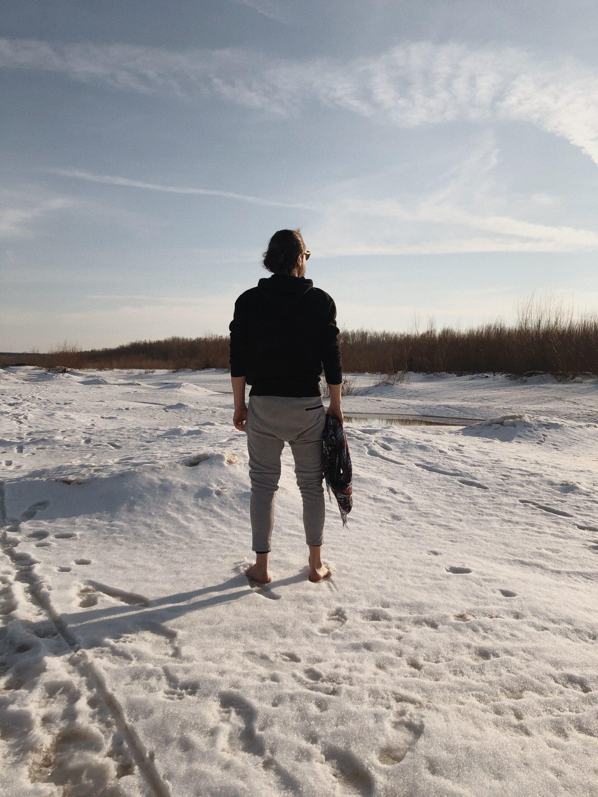 mężczyzna stojący boso na śniegu